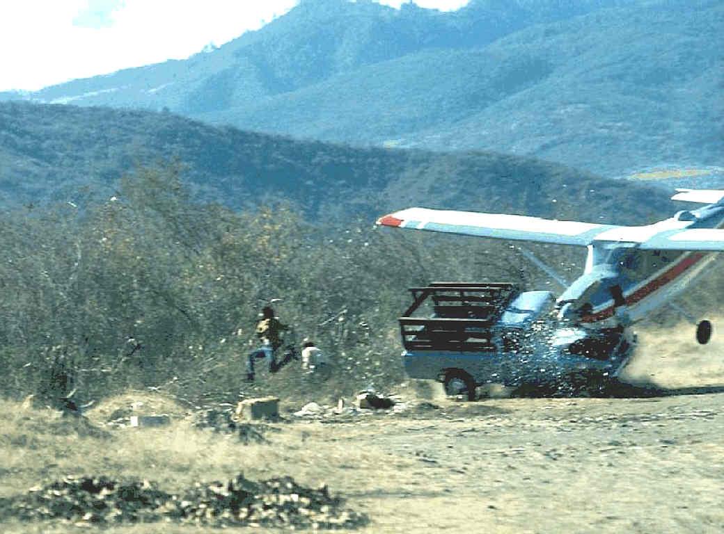 1976. Az erős keresztszél miatt a leszálló kisrepülő a pálya szélén álló kisteherautónak ütközik. Senki sem sérült súlyosan. Sanarate, Guatemala..jpg