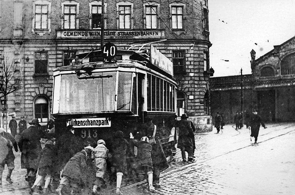 1934. Az osztrák polgárháborúban az éppen kikapcsolt áramszolgáltatás idején az utasok tolják a bécsi villamost..jpg
