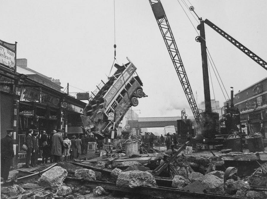 1940. október. A Balham High street éjszakai bombázásától beszakadt az utca alatti aluljáró menyezete és a 88-as busz az elsötítés miatt a bumbakráterbe esett. A képen a roncs másnapi kiemelése látható..jpg
