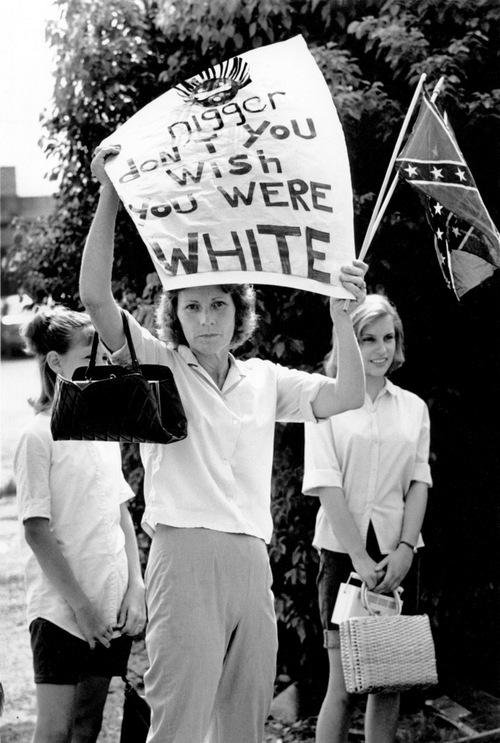1965. A feketék egyik civil jogi felvonulása mentén lányaival megjelent ellentüntető asszony. A tábla felirata Nigger ne akarj fehér lenni. Bogalusa, Louisiana..jpg