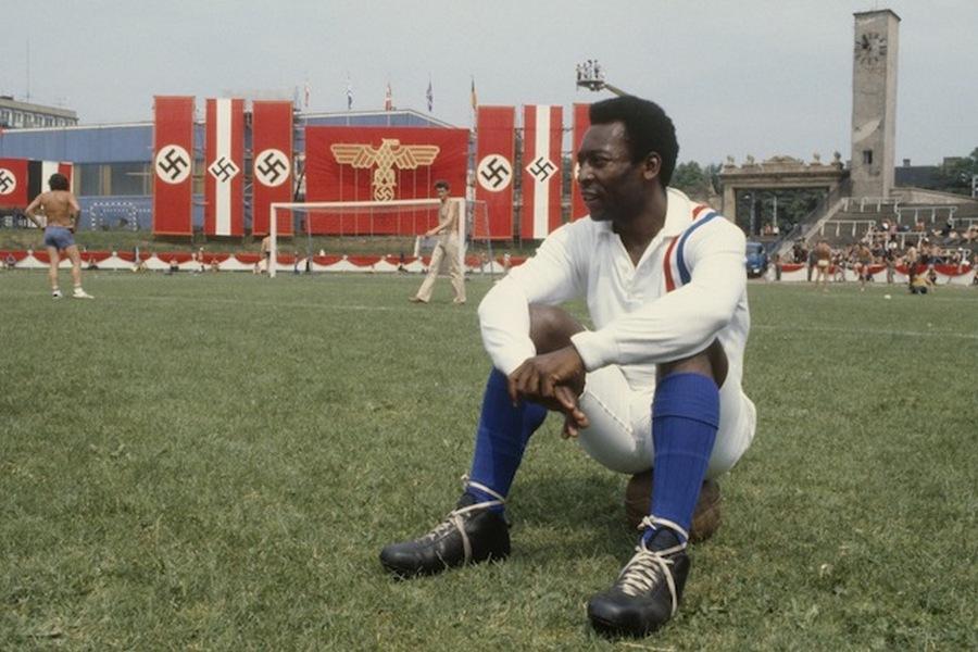 1980. A Menekülés a győzelembe című film forgatásának szünetében Pelé ül az MTK pályán..jpg