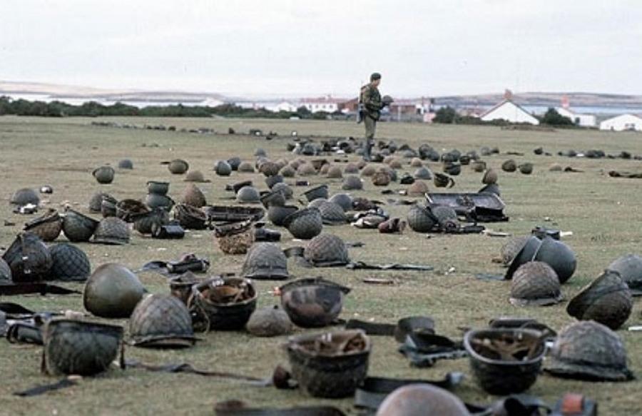 1982. május. Brit katona nézegeti az eldobált argentin sisakokat a Goose Green-i csata után a Falkland-szigeten..jpg