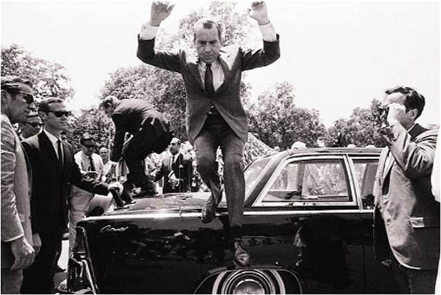 1969. Lahore, Pakisztán. Nixon amerikai elnök ugrik le az őt és a pakisztáni elnököt szállító limuzin csomagtartójáról. Háttérben a pakisztáni elnököt segítik le. Hogy miért másztak ki a nyitott tetőn.jpg