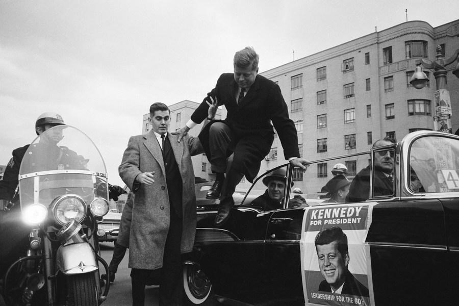 1960_kennedy_ugrik_ki_a_nyitott_gepkocsibol_egyik_valasztasi_kampanyutja_soran_bronx-ban_.jpg