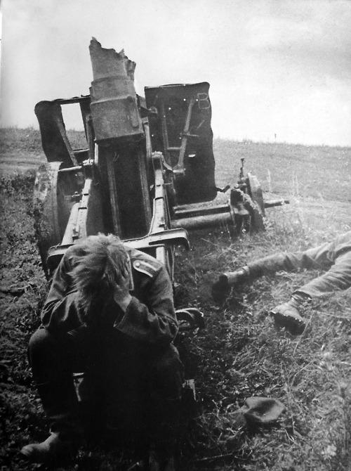 1943. Kurszk. Az elveszett ütközet után német katona ül a felrobant löveg mellett..jpg