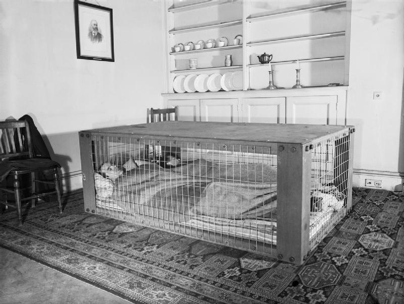 1940. Brit pár alszik az úgynevezett Morrison ketrecben, amit a bombázáso alatt összeomló házak elleni védelemre terveztek..jpg