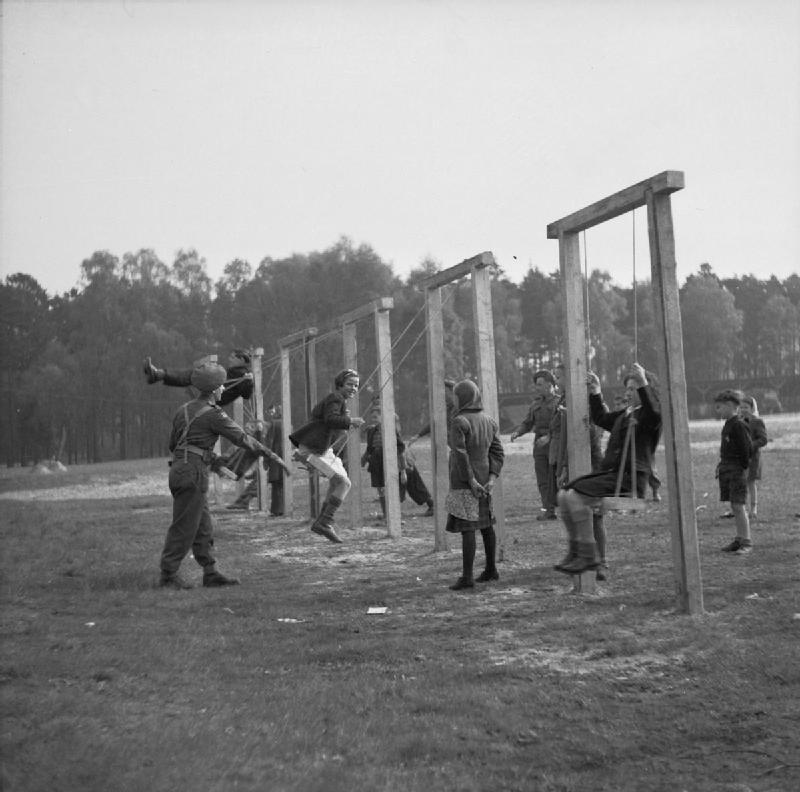 1945. Április 15. Belsen-i koncentrációs tábor közelében kiszabadított gyerekekkel játszanak brit katonák..jpg