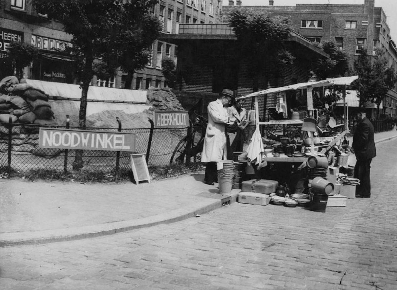 1940. Német bombázás után rotterdami kereskedő a boltja romjai közelében árusít..jpg