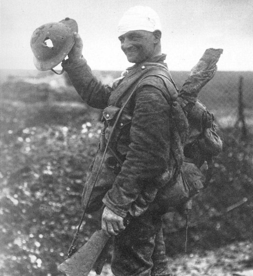 1918. Német katona mutatja a sisakját, amely bár kilyukadt, de megvédte a halálos fejlövéstől..jpg