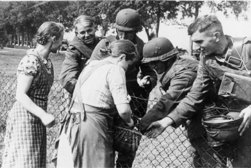 Helyi német nemzetiségű nők élelmiszert osztanak a német katonáknak.