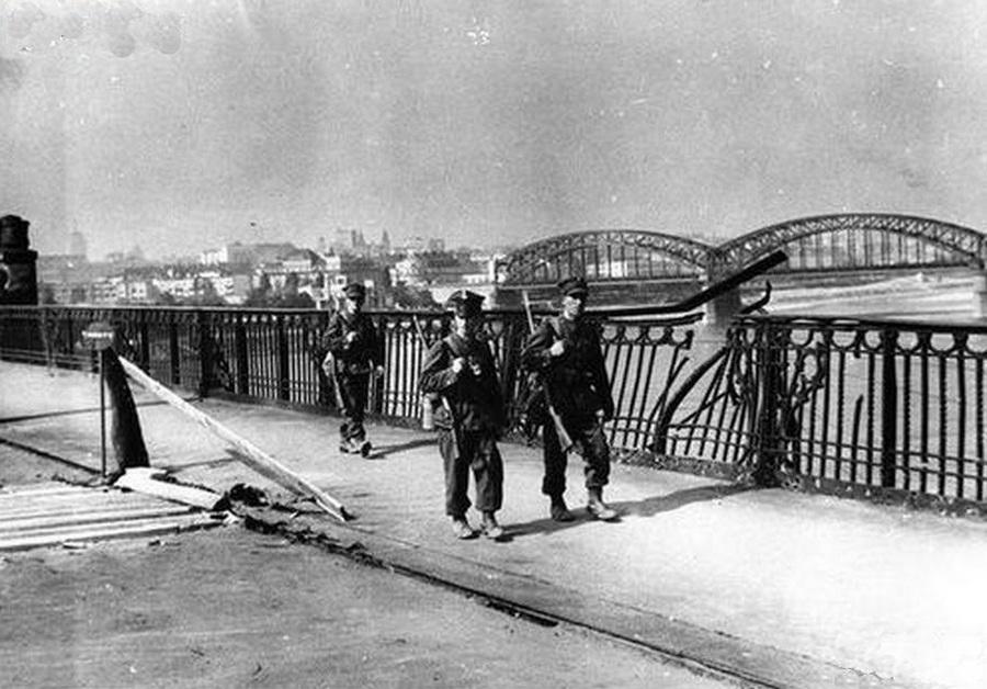 Lengyel katonák Varsóban egy bombázásban sérült hídkorlát mellett.