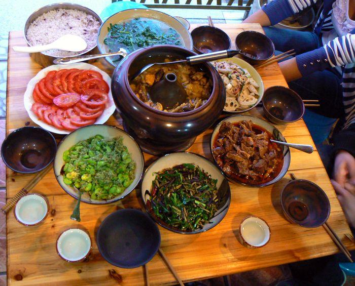 """Egyik vendéglátónk által készített """"qiguo ji"""" egyéb házias  Yunnan-i étellel együtt tálalva."""